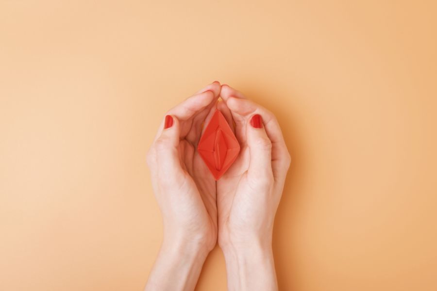 A Red Paper Boat Protectively Covered by a Woman's Hands